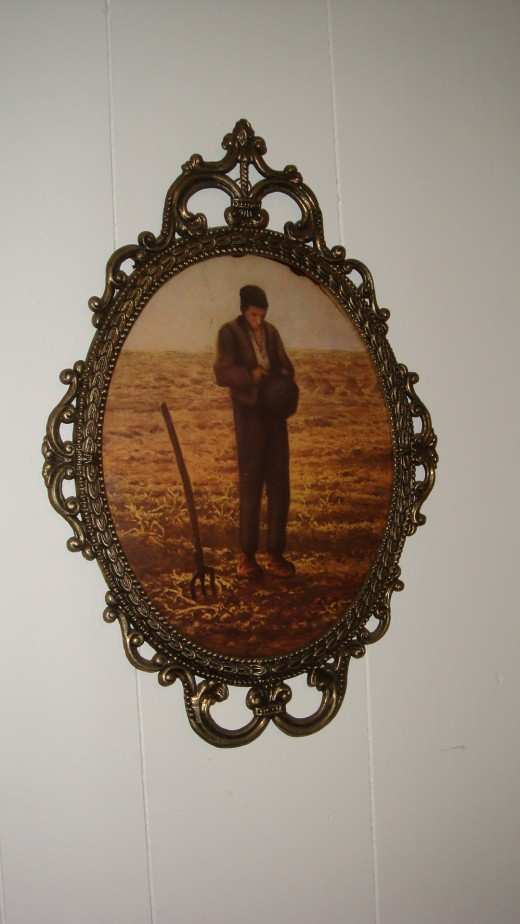 A vintage bubble glass frame, pictures a man looking down at his crops soil.