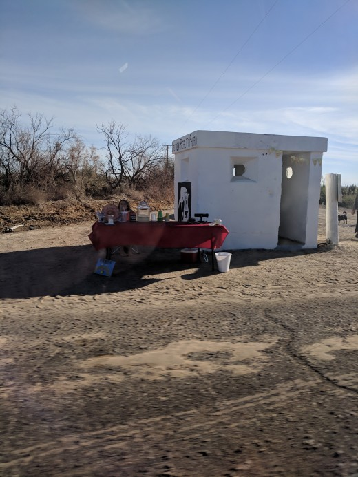 Woman in Colorado Desert south of California's Salton Sea who appears to be selling or giving away lemonade.