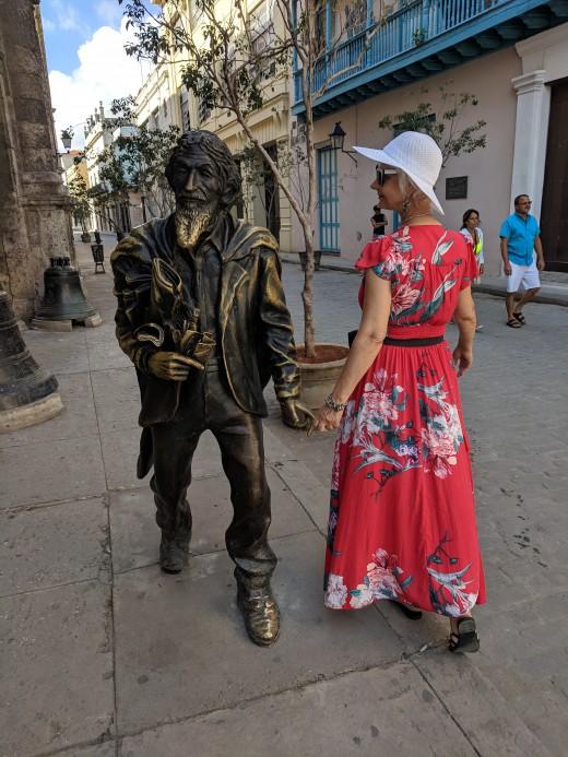 My wife admiring sculpture of Joaquin E. Weiss located in front of the Basilica de San Francisco de Asis in Havana, Cuba