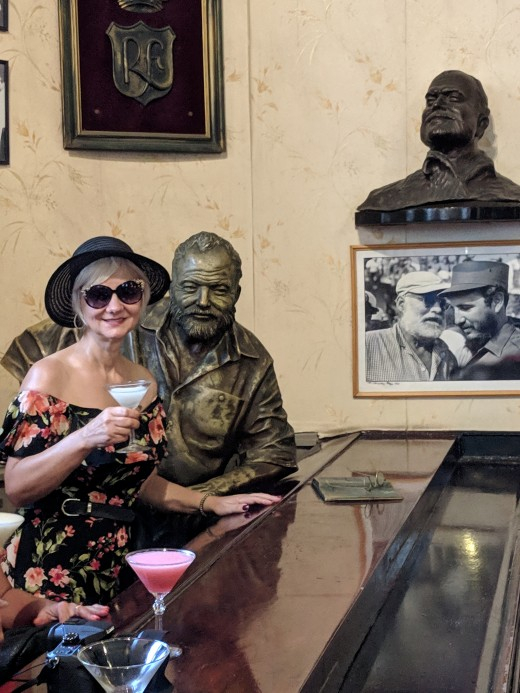 My wife enjoying a daiquiri at bar next to sculpture of Ernest Hemingway  in La Floridita Bar in Old Havana - this was one of Hemingway's favorite drinking spots