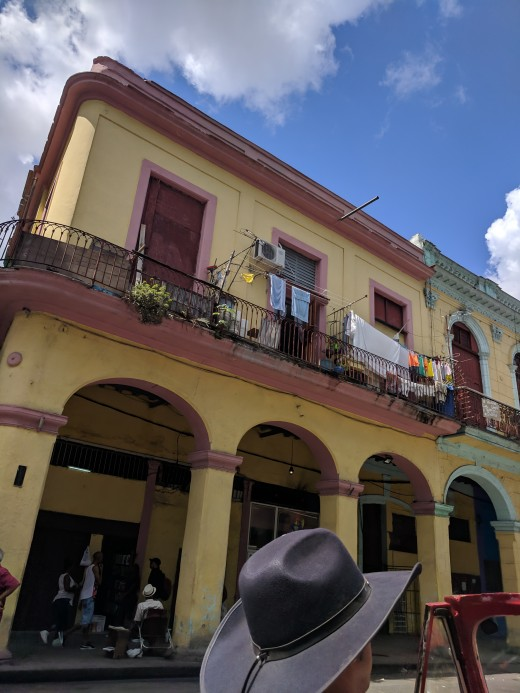 Another picture taken from our car (can see our driver's hat in bottom center)  This is typical of most of Havana - Few new and restored buildings are for tourists