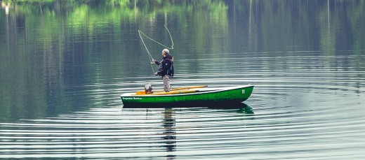 Fly fishing from a boat on a lake.