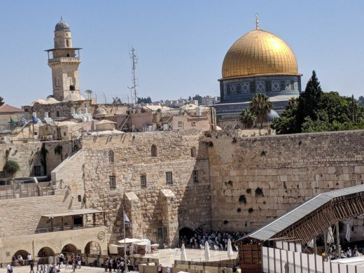 Jewish people pray at the Western Wall while the Muslim Dome on the Rock towers above them.