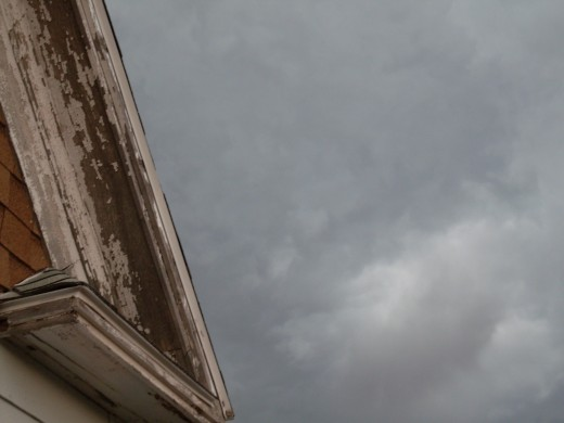 Clouds above the eaves of the house. The air is perfectly still.