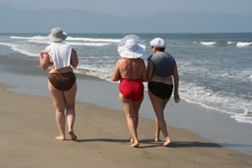 Three older women walking along the beach, not yet in great shape, but enjoying the exercise and the fresh air.