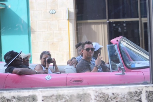 Riding in a pink convertable through Old Havana, our reflections in the windows of one of the more modern buildings circa '50s.