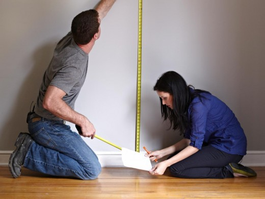 Preparing wall through measuring its size.