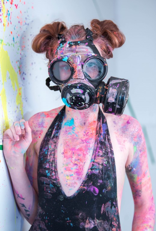 A lady wearing a gas mask and splatters of paint cover her body.