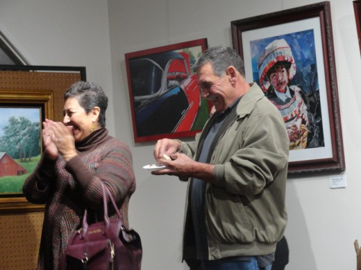 One of my paintings on the right at an art show reception.