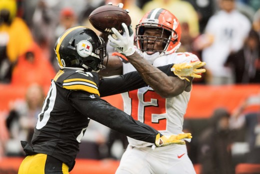 Cleveland Browns wide receiver, Josh Gordon (12), catches a touchdown as Pittsburgh Steelers cornerback, Cameron Sutton (20), defends in a 2018 game. Gordon is Cleveland's single-game and single-season record holder for receiving yardage.