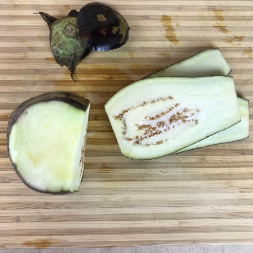 Cut off the top and bottom of the eggplant, and slice it lengthwise into 1/2 inch slices.