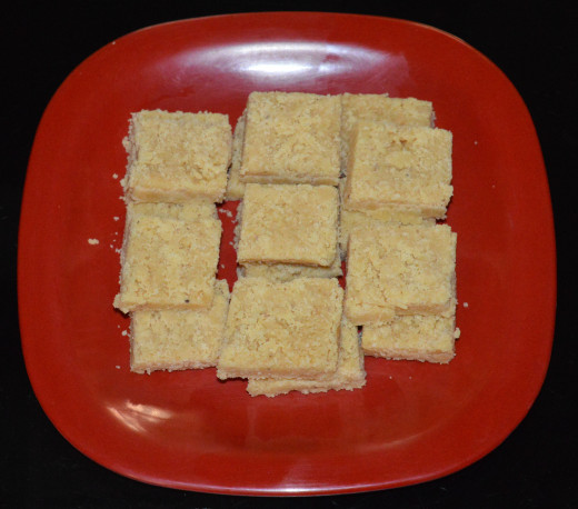 Insert the knife deep on the lines and cut it. Separate the pieces. Arrange coconut and chickpea flour burfi on a plate. Enjoy eating the delicious and flavorful dessert!