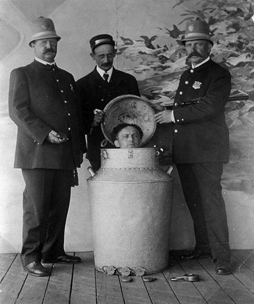 Harry Houdini being placed in milk jug