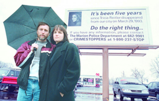 Tricia Reitler's parents Garry and Donna standing in front of a billboard on 41st Street and Western Avenue in 1998, five years after Tricia's disappearance.
