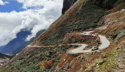 The meandering road, towering mountains, and white clouds