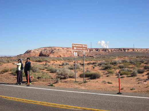 Road sign for Horseshoe Bend showing avid tourists who parked along US 89 (not permitted).