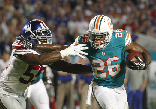 Miami Dolphins running back, Lamar Miller (26), stiff arms New York Giants linebacker, J.T. Thomas, on his way to a touchdown in a 2015 game.
