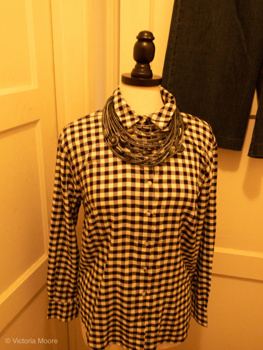 Black and white checked shirt accessorized with African necklace.