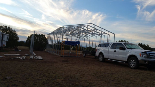 The frame of the main building is up. An important note if your building is similar: until siding goes up or hat channel on the roof, clamp 2x4s between uprights to keep them stable and from bending or swaying in the wind or from their own weight.