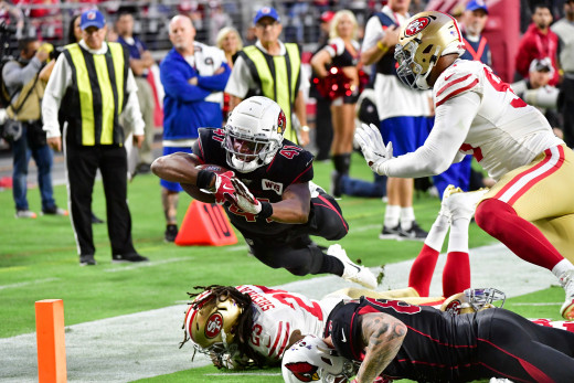 Arizona Cardinals running back, Kenyan Drake, dives over San Francisco 49ers cornerback, Richard Sherman, to score a touchdown in a 2019 game at State Farm Stadium. Drake has the potential to be the next great running back for the Cardinals.
