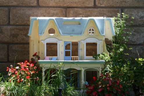 My daughters' old dollhouse now nestles amist herbs, waxed begonias, and natural elements like mossy wood and pebbles.