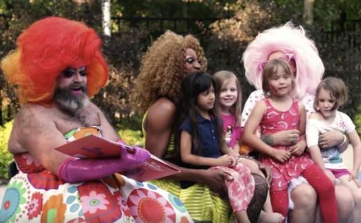 Men in drag holding children at drag queen story hour