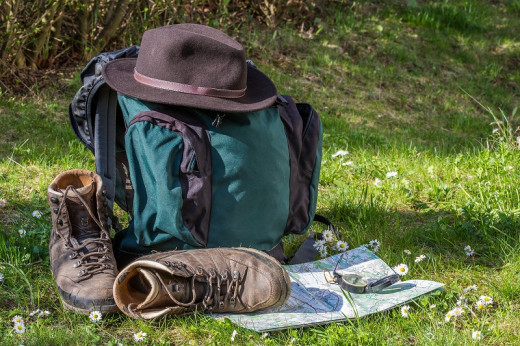 A well-equipped walker has a day-sack, comfy shoes, shady hat, compass, and map.