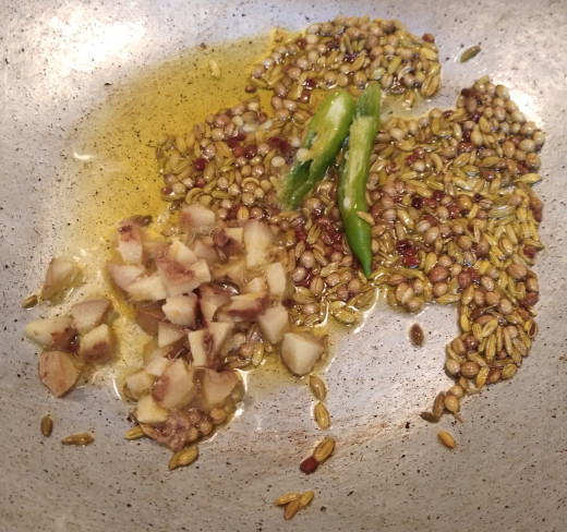 Add chopped ginger and slit green chilies. Fry till ginger starts smelling good.