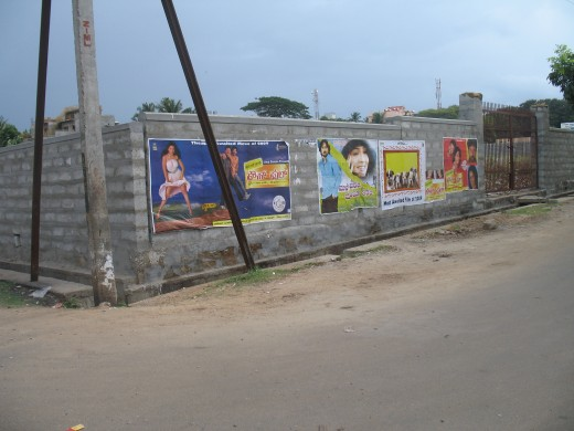 Cinema posters pasted at midnight on vacant site compounds.
