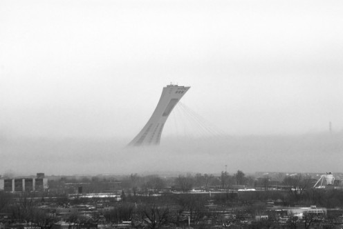 Olympic Stadium rising through winter fog at dusk, Montreal, Quebec