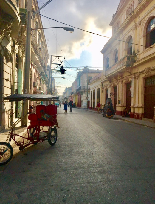 After heavy rainfall. A small child is resting under the roof of a bicycle taxi in Centro Havana.
