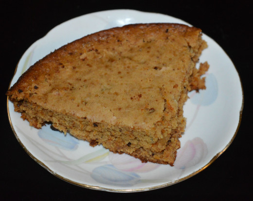 Once the cake is done, turn off heat. Take the container out and set aside for cooling. When it cools down, run a knife along the edge. Invert it on a plate. Cut the cake to your desired shape and size. Enjoy eating the yummy carrot cake!