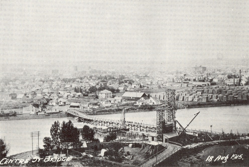 Scanned photo of Calgary's Centre Street Bridge under construction in 1915. Looking Southwest across the Bow River toward downtown
