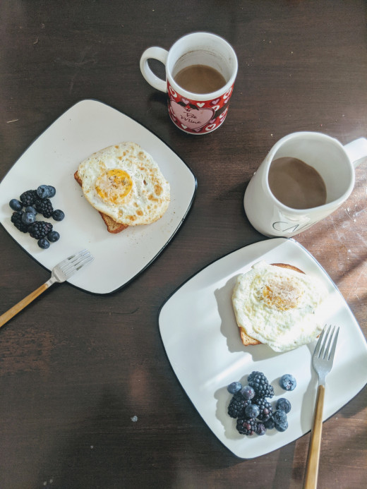 Sola bread toast with a fried egg, with a side of berries.