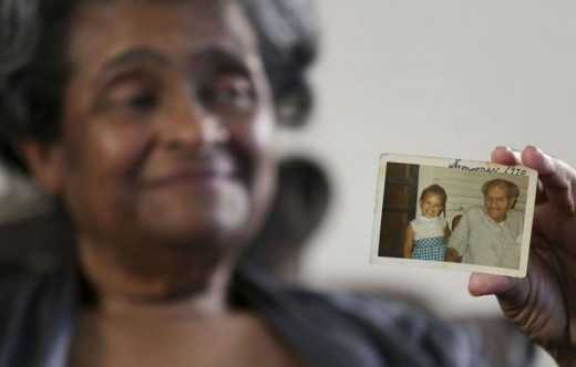 Bettye Milner holds a picture of her murdered daughter Denise Milner. Photo courtesy of Tulsa World.