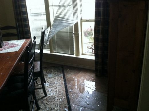 Before  repairs.  Dining room and windows hail damage. Note the broken glass on the floor, water and blinds being blown back.