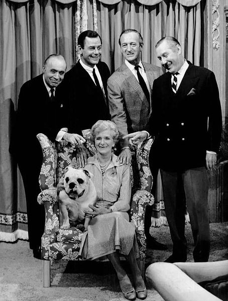 """Cast photo of the television program The Rogues. Seated with the bulldog is Gladys Cooper """"Auntie Margaret"""". Standing from left: Charles Boyer """"Marcel St. Clair"""", Gig Young """"Tony Flemming"""", David Niven """"Alec Flemming"""", and Robert Coote """"Tim St. Clair"""