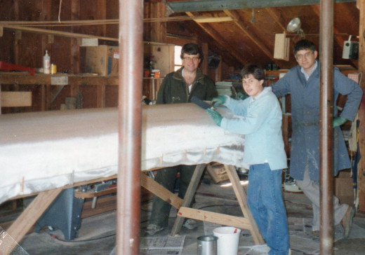 Scott and me with fiberglass cloth draped over the canoe. Our friend, Will instructing us on how to apply epoxy resin and make a water-tight finish.