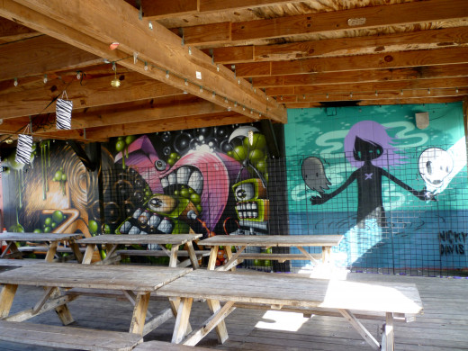 Covered picnic area outside at Cecil's Pub with Nicky Davis Mural among others