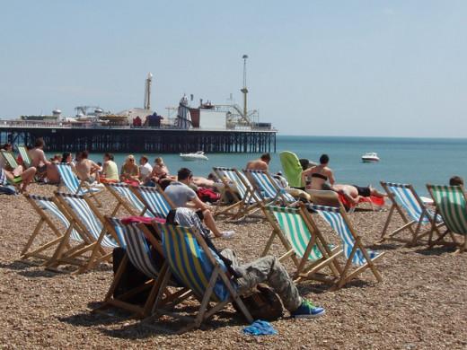 Sunbathers in Brighton Beach, UK enjoy the benefits of lying in the sun