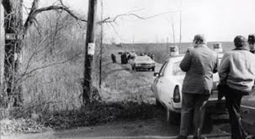 Police detectives investigate the location where Michelle Maenza was found on the side of a rural road in Macedon, New York.