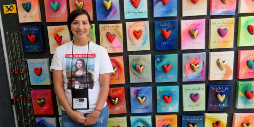 Artist Dania Olivares was standing in front of some of her mixed media pieces.