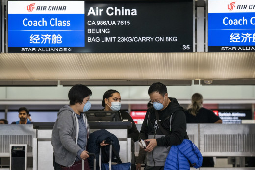 Travelers with face masks check in at the Air China counter at San Francisco International Airport in late January