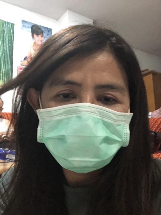 A pretty Thai girl defends against infection in Thailand's streets.