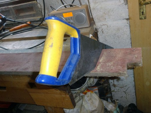 Squaring off one end of the back panel with a handsaw.