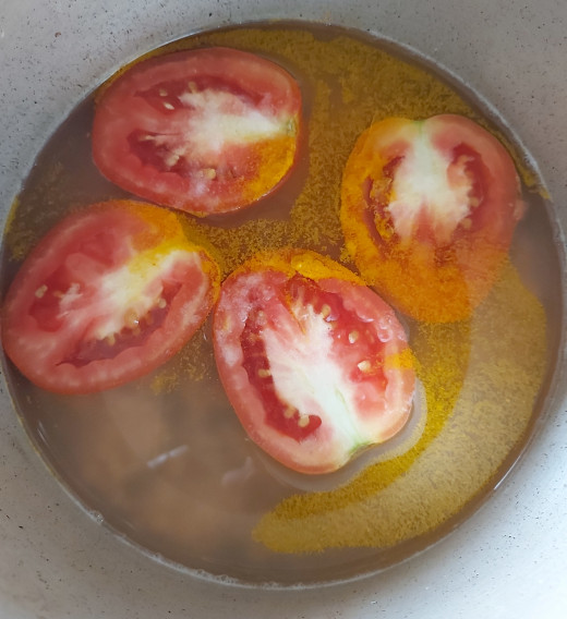 Wash properly. Add 1-2 cups of water, 2 roughly chopped tomatoes, 1/2 teaspoon turmeric powder, and a pinch of salt.