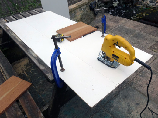 Using a jig saw to cut the white faced hardboard to size.