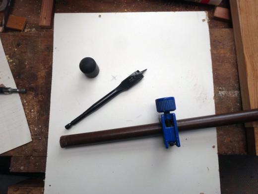 Metal rod to be cut with a pipe cutter, rubber foot for fitting to the bottom of the rod, and flat wood head bit to cut the hole for the rod.