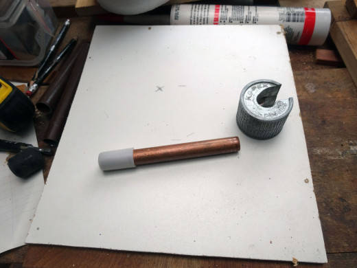 Copper pipe to be used to support one of the polystyrene heads cut to length with a pipe cutter.
