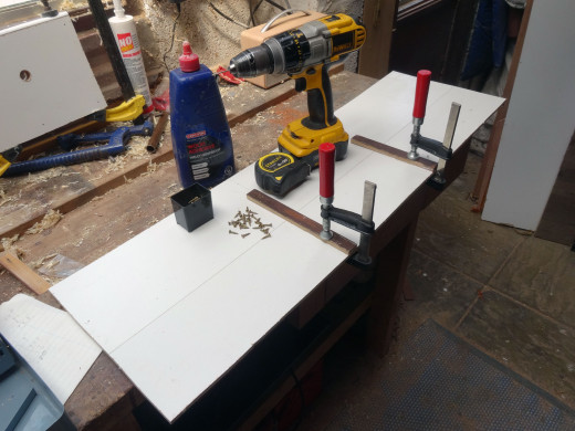 Fitting shelf supports to one of the white faced hardboard side panels.